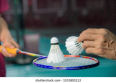 Badminton player holding racket with used BADMINTON shuttlecock on top and hand of service judge hold new shuttlecock to change the new one with blur background.