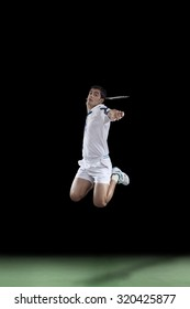 Badminton player leaps high in the air and prepares to smash a shuttlecock