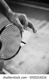 A badminton player serving the shuttlecock