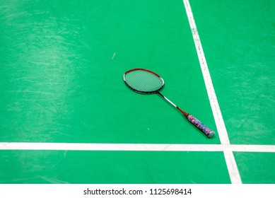 badminton racket on green court.