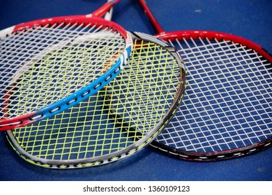 badminton rackets lying on the blue wooden floor of the sports field. Three badminton rackets lying ropna floor in the gym, closeup.