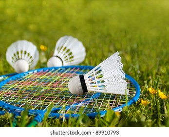Badminton rackets with shuttlecock on the grass.
