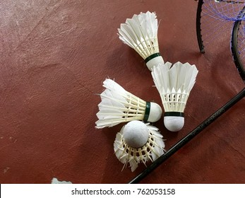 Badminton shuttercock on red colour floor with broken racket