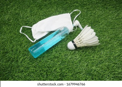 Badminton shuttlecock with hand gel and face mask to prevent virus and pollution on green grass