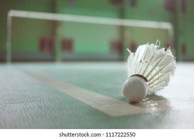Badminton shuttlecock on green court