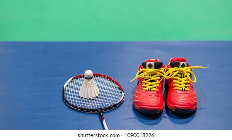 badminton shuttlecock on racket and red shoe on badminton court.