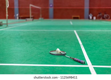 badminton shuttlecock and racket on green court.