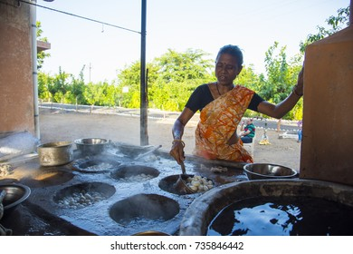 BADNERA, MAHARASHTRA, INDIA 4 OCTOBER 2017 : Unidentified women are soaked silkworm cocoons in hot water, and the delicate thread is wound onto a machine that unravels the cocoon.