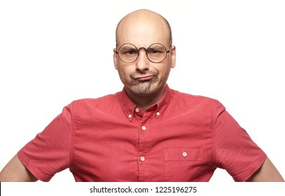 bad-tempered person. Bald man with sceptical expression of his face wearing spectacles. Isolated