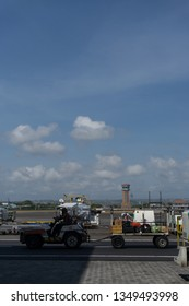 BADUNG.BALI/INDONESIA-AUGUST 07 2018: ATC tower at Ngurah Rai Bali Intenational airport from the further. Some mobile vehicle pull the suitcase container to the plane.