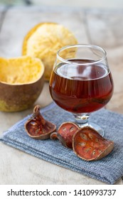 Bael fruit tea - A glass of Bael fruit tea and dried fruit Bale beverage On Wooden background.
