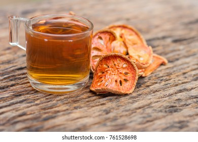 Bael fruit tea - A glass of Bael fruit tea and dried fruit on a rustic wooden background, Bale beverage