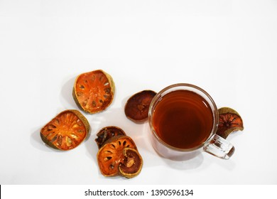Bael juice, in clear glass containers, with bael fruit slices Placed beside, on a white background.