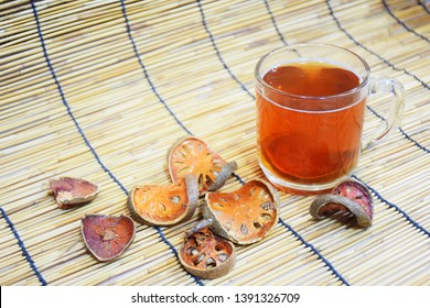 Bael juice, in clear glass containers, with bael fruit slices Placed beside, Folk herbs, medicinal properties.