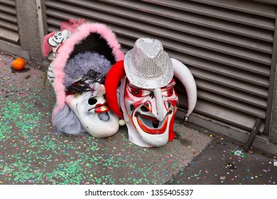 Baeumleingasse, Basel, Switzerland - March 12th, 2019. Close-up two carnival masks laying on the ground