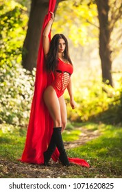 Baeutyful sexy fitness woman with red canvas on a nature.