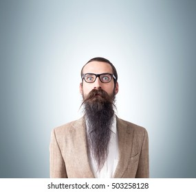8a493826895 Baffled man wearing glasses and long beard is standing against gray  background. Concept of eccentric