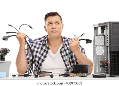Baffled young guy holding a bunch of computer wires and looking up isolated on white background