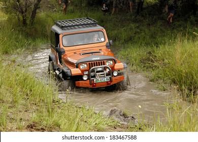 BAFOKENG - MARCH 8: Crush Beige Jeep Wrangler Off-Roader V8 crossing muddy pond obstacle at Leroleng 4x4 track on March 8, 2014 in Bafokeng, Rustenburg, South Africa