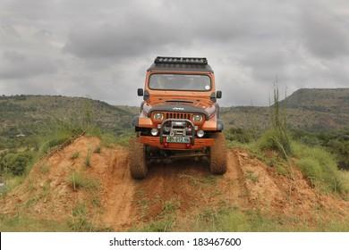 BAFOKENG - MARCH 8: Crush Beige Jeep Wrangler Off-Roader V8 crossing obstacle at Leroleng 4x4 track on March 8, 2014 in Bafokeng, Rustenburg, South Africa