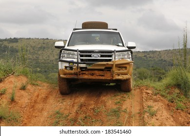 BAFOKENG - MARCH 8: White Ford XLT Supercab 3.0L TDCi with silver canopy crossing obstacle at Leroleng 4x4 track on March 8, 2014 in Bafokeng, Rustenburg, South Africa