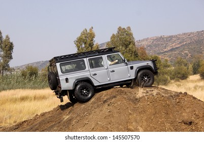 BAFOKENG - MAY 18: Silver Land Rover Defender 110 SW scaling high sand dune obstacle at new 4x4 track opening event May 18, 2013 in Bafokeng, Rustenburg, South Africa