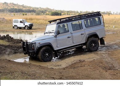 BAFOKENG - MAY 18: Silver Land Rover Defender 110 SW going through water obstacle at new 4x4 track opening event May 18, 2013 in Bafokeng, Rustenburg, South Africa