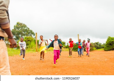 Bafoussam, Cameroon - 06 august 2018: young smiling african girls and boys running and having fun outside poor village school during summer