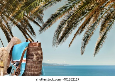 bag and accessories for the beach under palm leaves with sea background
