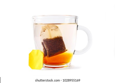 A bag of black tea in a glass cup on a white background. A traditional English drink on isolated