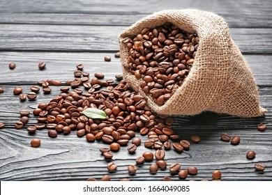 木の背景にコーヒー豆の袋