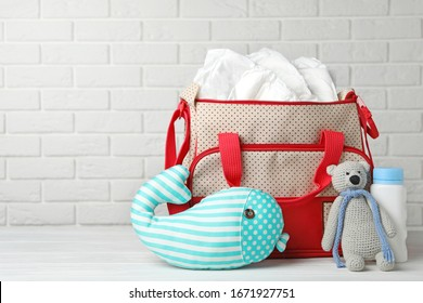 Bag with diapers and baby accessories on wooden table against white brick wall