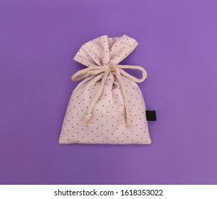 Bag of dried lavender with polka dot pattern fabric, organic and natural lavender bag close up with macrame rope on purple background