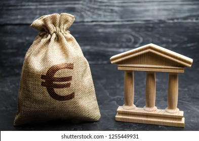 A bag with euro money and a bank or government building. Deposits, investment in the budget. Grants and subsidies. Payment of taxes. Central bank. Credit tranches and leases. Debt repayment.