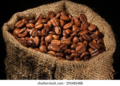 bag filled with coffee beans in spotlight on black background