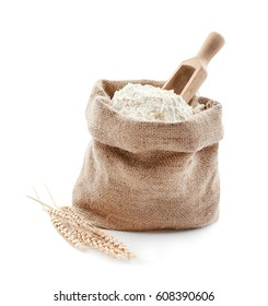 Bag with flour and wooden scoop on white background