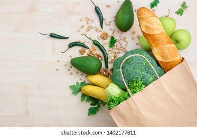 Bag food concept. Groceries shopping paper bag with healthy food on a wooden background top view