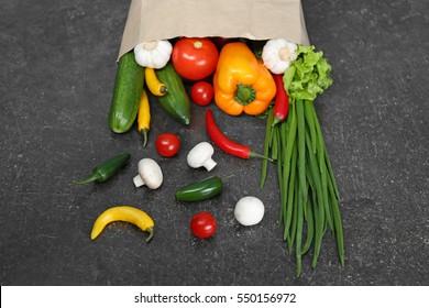 Bag of fresh vegetables on gray background