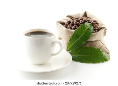 Bag full of coffee beans with green leaves and coffee cup on white