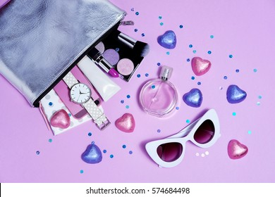 Bag girl with accessories and candies on purple flat lay. Sweet style sunglasses, watch, perfume , rings and diary. Overhead