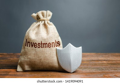 Bag with the inscription investment and shield. Guarantee of protection of foreign investment in the economy, the creation of favorable conditions for attracting investors, capital protection.