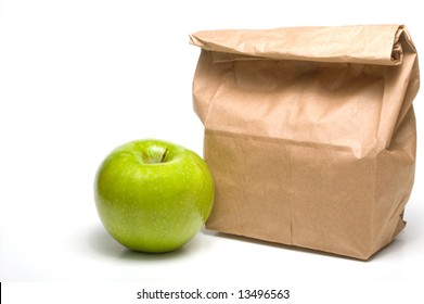 A bag lunch with a Granny Smith apple.