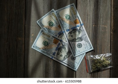 The bag of marijuana lies on dollars on wooden background. Weed. Drugs