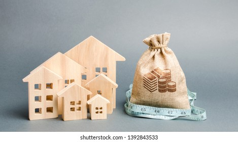 Bag with money and tape measure with a wooden houses. The concept of a limited real estate budget. Low subsidies. Lack of investment in construction. Market crisis. Reduced demand for home buying.