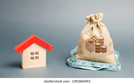 Bag with money and tape measure with a wooden house. The concept of a limited real estate budget. Low subsidies. Lack of investment in construction. Market crisis. Reduced demand for home buying
