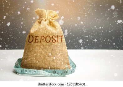 Bag with money and tape measure and the word deposit. The concept of the New Year's deposit. New Year's interest rates. Stocks Convenient and profitable offers. Christmas and seasonal deposits in bank