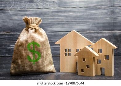 A bag with money and three houses. Concept of real estate acquisition and investment. Affordable cheap loan, mortgage. Taxes, rental income. Building houses. Municipal budget of the community.