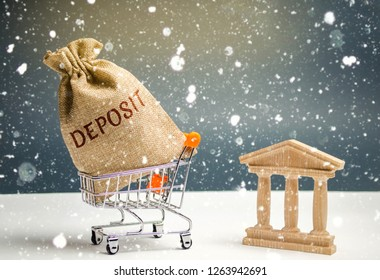 Bag with money and the word deposit with bank building. The concept of the New Year's deposit. New Year's interest rates. Promotion Convenient and profitable offers. Christmas and seasonal deposits