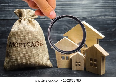 A bag with money and the word Mortgage and a wooden houses. The accumulation of money to pay interest rates on mortgages. Buying a property in debt. Take credit for housing. Loan for housing.