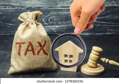 A bag with money and the word tax next to a wooden house. Taxes on real estate, payment. Penalty, arrears. Register of taxpayers for property. Law-abiding, evasion of payment. Court law